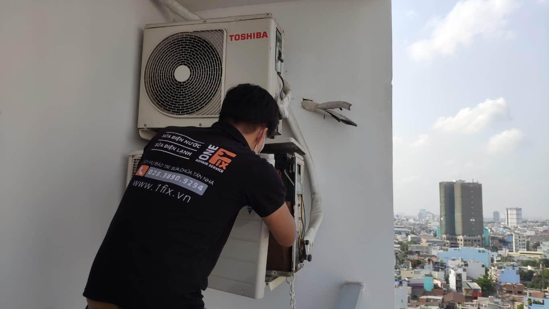 Thợ sửa máy lạnh 1FIX™ tháo dàn nóng để tiến hành kiểm tra Board điều hòa